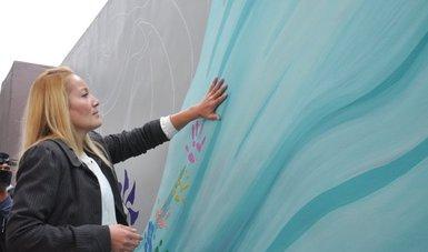 Una mujer plasma su mano sobre la pared del Centro de Justicia para las Mujeres en Jalisco en su primer aniversario