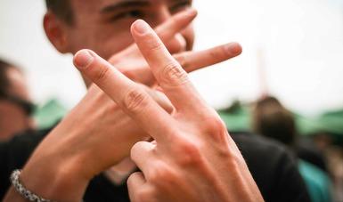 Imagen de un joven que hace la señal de tag con las manos.