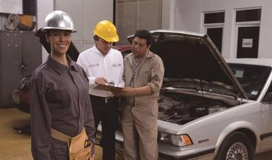Mujer sonriendo adelante de dos hombres revisando unas hojas de trabajo.