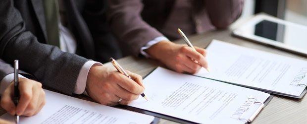 tres personas firmando un convenio