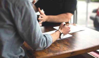 Imagen de dos personas hablando y escribiendo en una hoja sobre una mesa.