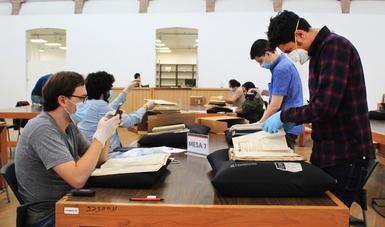 Foto de sala de consulta A del AGN, se observa una mesa con documentos y usuarios leyéndolos