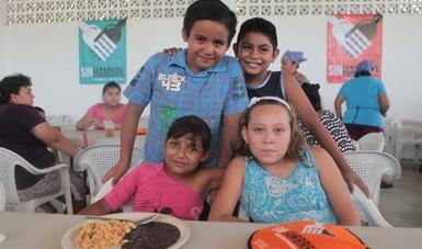 Dos niños y dos niñas sonriendo juntos en un comedor comunitario
