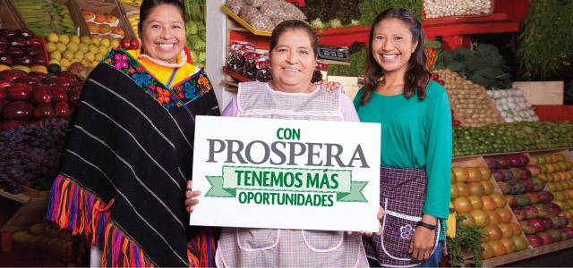 """Tres mujeres en un mercado de fruta sostienen un letrero que dice """"Con Prospera tenemos más oportunidades"""""""
