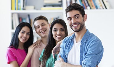 Imagen de 4 chicos sonriendo en una oficina.