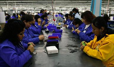 Mujeres trabajando en ambos lados de una mesa, uniformadas con trajes azul y amarillo.