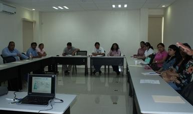 Grupo de personas sentados alrededor de una mesa recibiendo una capacitación, hombres y mujeres.