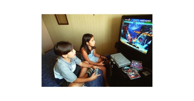 Niña y niño usan videojuego.
