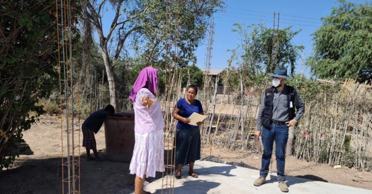 En la imagen se aprecia a dos personas beneficiarias de la Comisión Nacional de Vivienda (Conavi), en un inicio de obra junto con personal de la comisión, resolviendo asesoría respecto a su proyecto de vivienda.