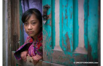 Niña de Chiapas se asoma por la puerta de su casa de madera.