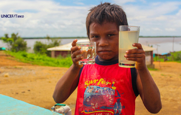 Niño vende agua en la calle.