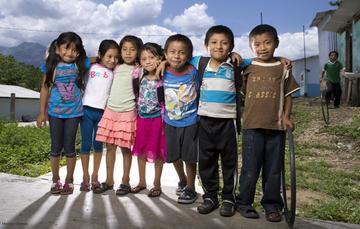 Niñas y niños en la cancha de deportes de su comunidad rural.