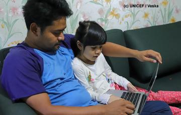 Padre e hija comparten una laptop.