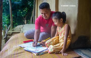 Niña y su padre platican sobre un dibujo que ella hizo.