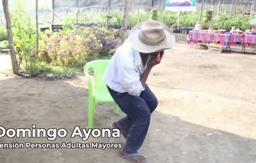 Domingo Ayona, persona adulta mayor tocando la armónica y bailando