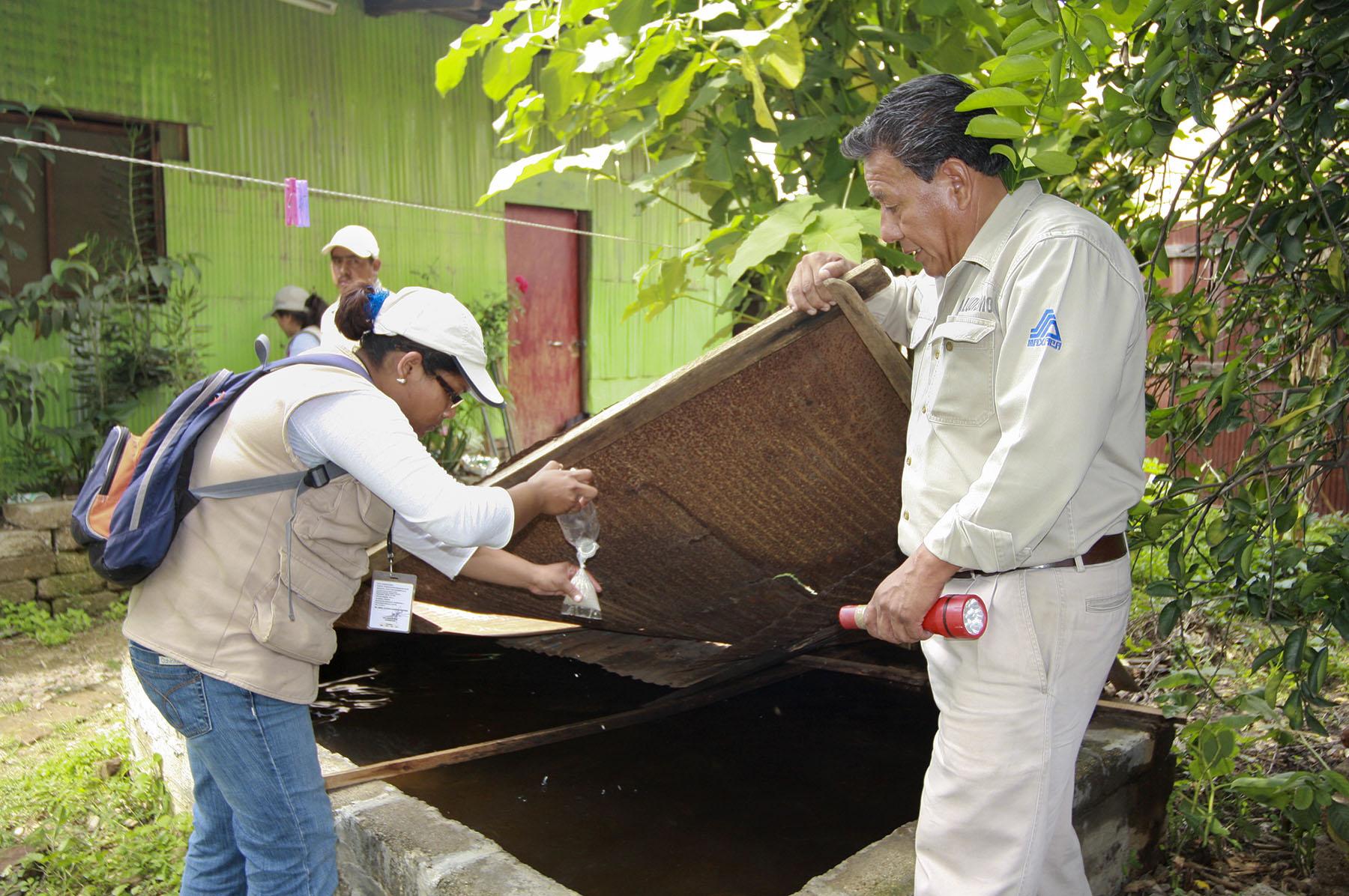 Hombre y mujer revisando sitios posibles de criaderos del zika.