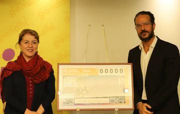 Fotografía de Margarita González Saravia Calderón y Alberto Achar con el billete develado de 50 años de librerías Gandhi