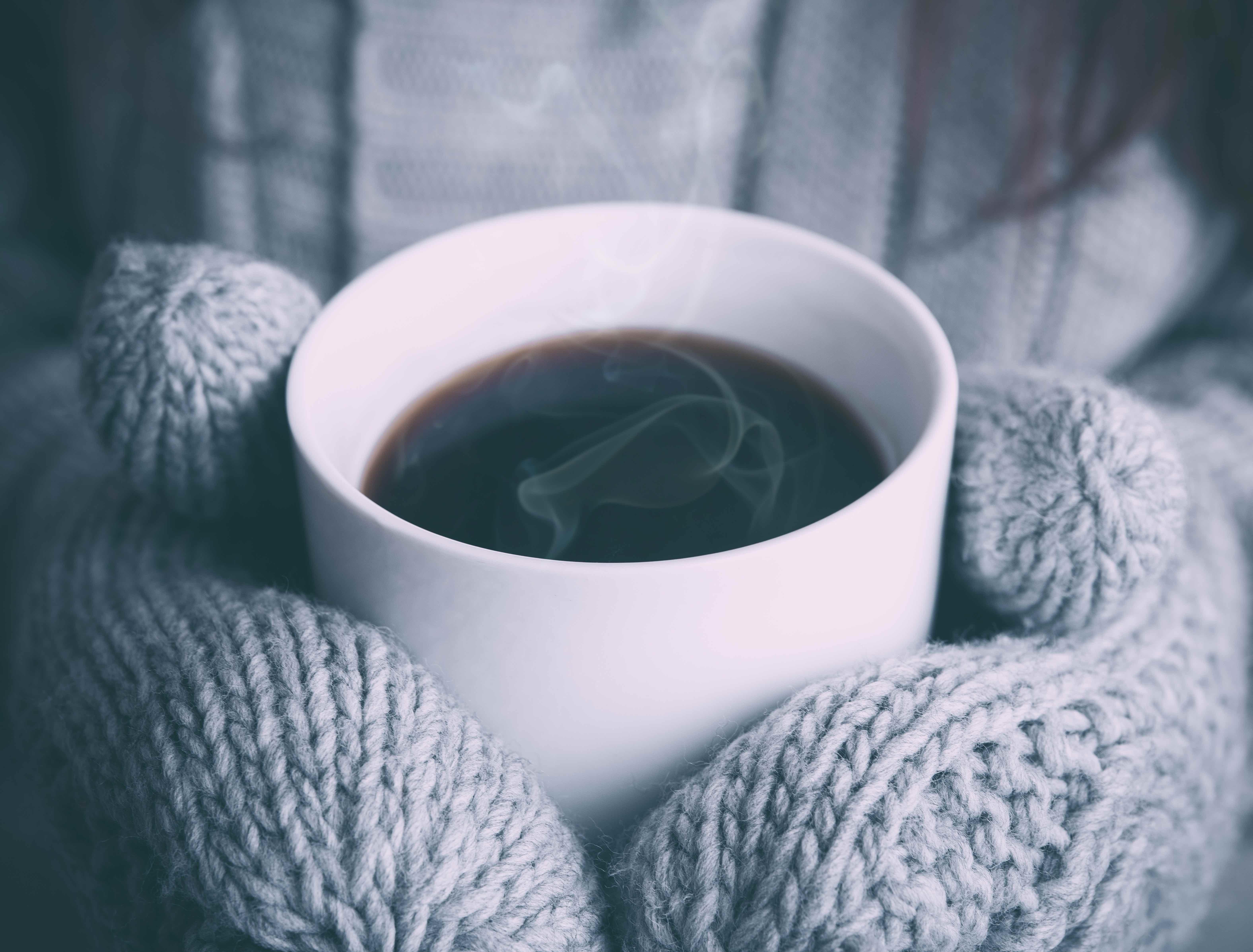 Una persona sostiene en sus manos, con guantes, una taza con una bebida caliente.