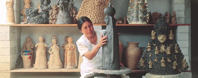 Artesana mexicana moldea arcilla para formar una escultura de La Virgen