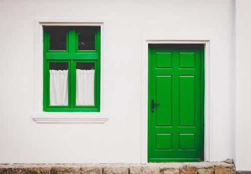 Fotografía de la vista de la calle de una puerta y ventana, en color verde, de un inmueble.