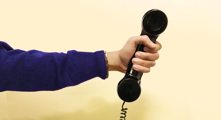 Imagen de una mano sosteniendo el auricular de un teléfono.