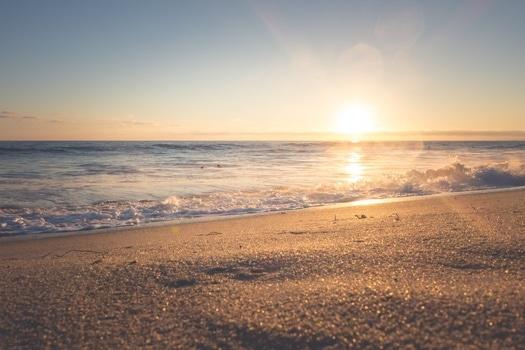 Fotografía de una playa con el sol al fondo