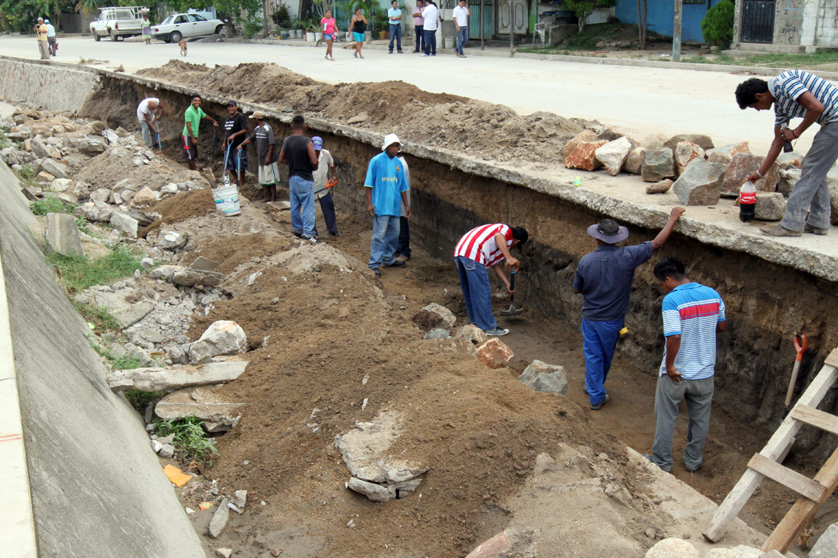 Trabajadores están poniendo asfalto en un camino.