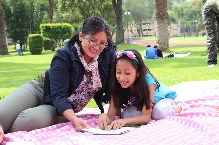 Madre e hija leen juntas en un parque, recostadas en el pasto. Ambas sonríen durante la lectura.