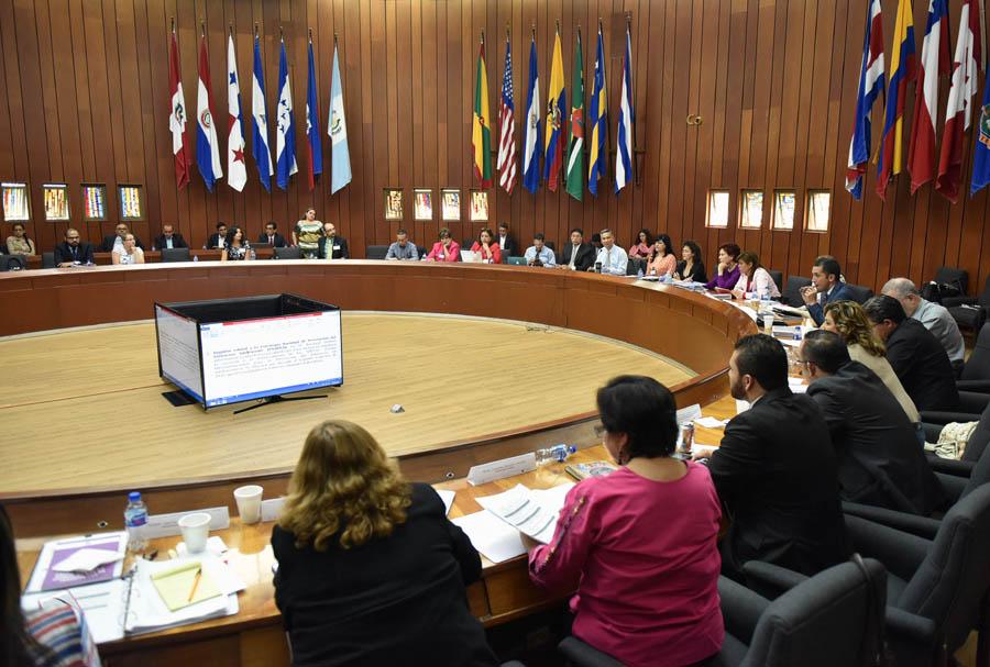 Las y los secretarios ejecutivos de los SIPINNA Nacional y Estatales, en mesa redonda, con monitores al centro y banderas de los países latinoamericanos.
