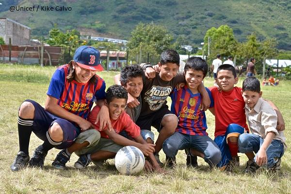 Siete niños y adolescentes, abrazados, sonrientes, miran un balón de futbol al centro, en una cancha llanera.