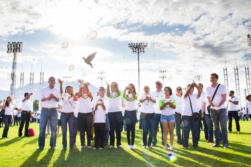 Varias personas en un acto recreativo lanzan al aire globos blancos y dejan salir a volar palomas blancas.