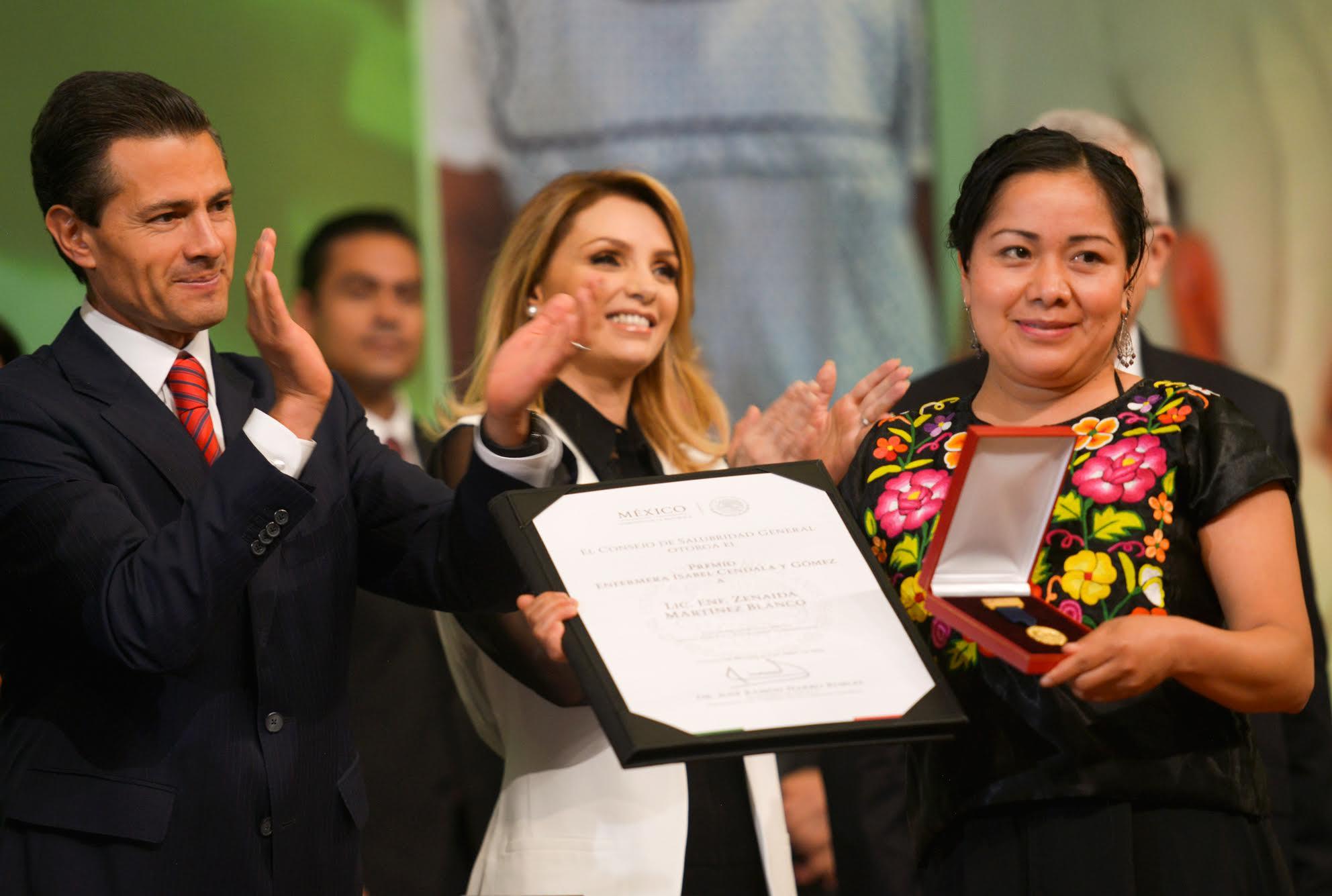 El Presidente Peña Nieto y su esposa, Angélica Rivera de Peña, entregan el reconocimiento a uno de los once mexicanos destacados en el sector salud en el año.