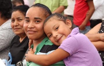 Dos mujeres y una niña abrazando a su mama.