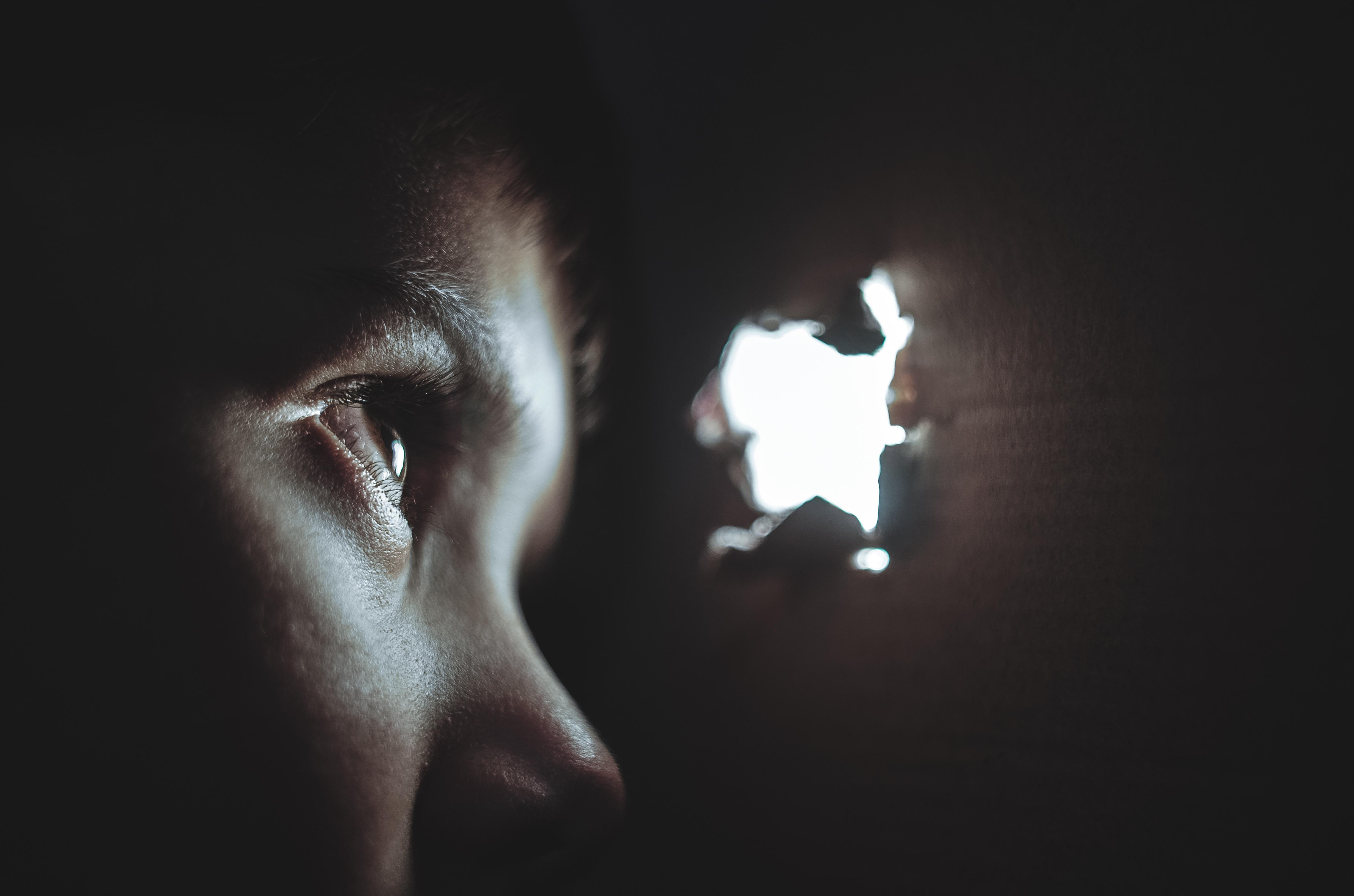 Fotografía de un niño viendo a través de un agujero en la pared.