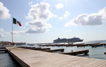 Bandera en un muelle y un barco cerca.