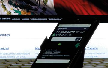 En la imagen se ve una computadora personal mostrando la imagen de gob.mx y enfrente un teléfono inteligente donde también se está viendo la primera página de Gob.mx