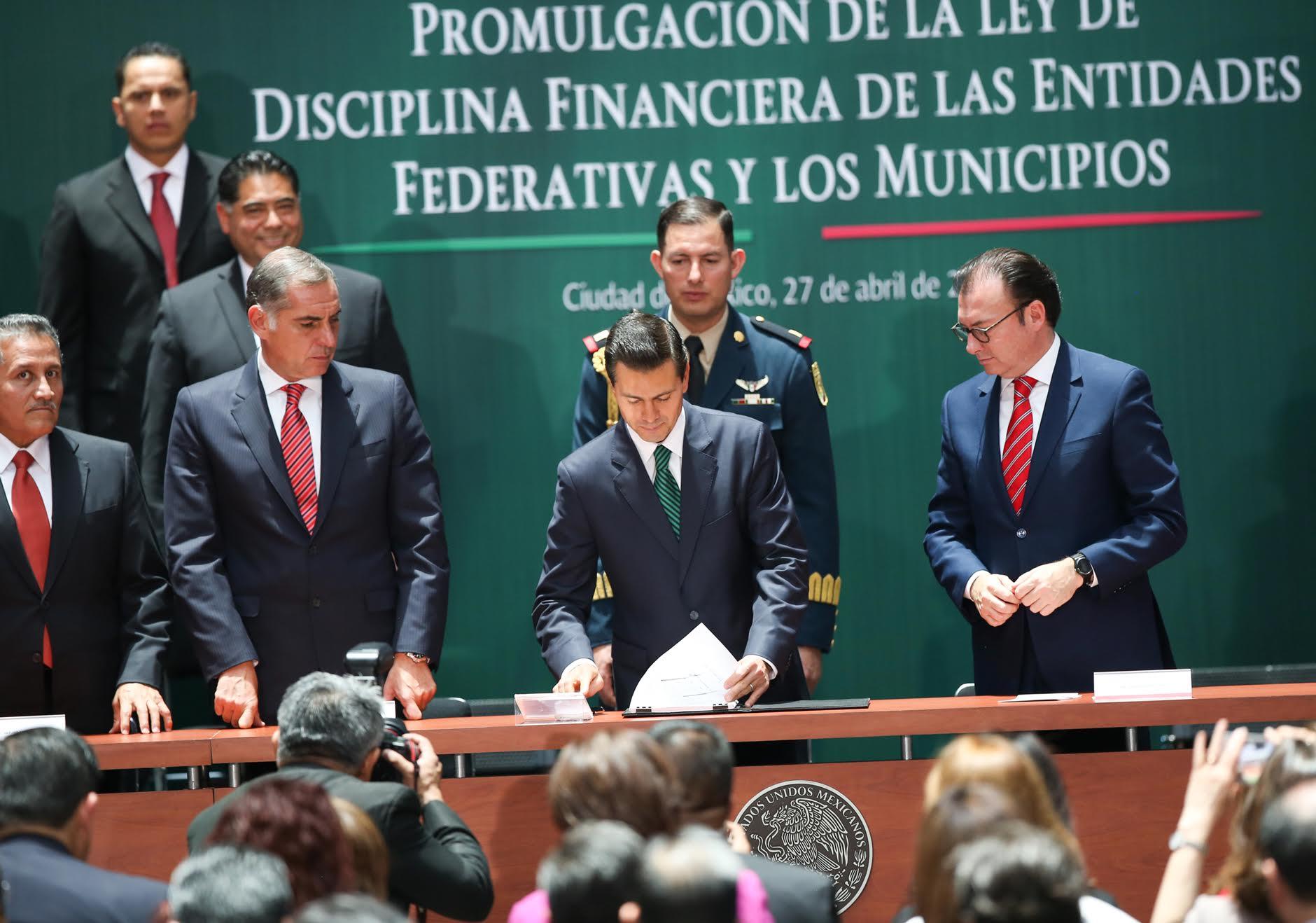 El Primer Mandatario firma el documento de la Promulgación de la Ley de Disciplina Financiera de las Entidades Federativas y Municipios, a su lado Luis Videgaray y Gabino Cué.