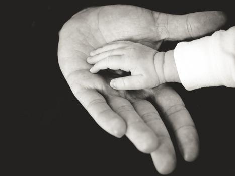 Mano de una persona adulta sostiene la mano de un bebé