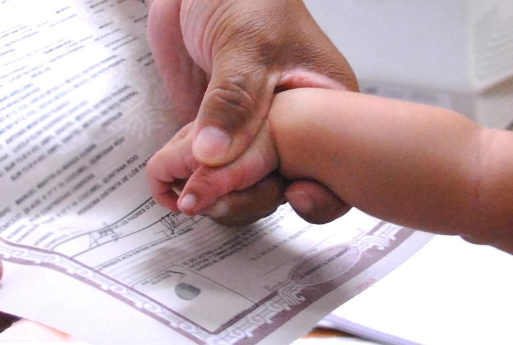 Fotografía de la mano de un bebé y un registro civil de nacimiento.