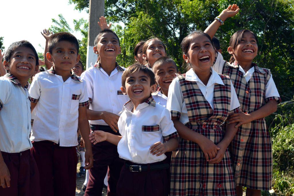 Niñas y niños en uniforme sonriendo