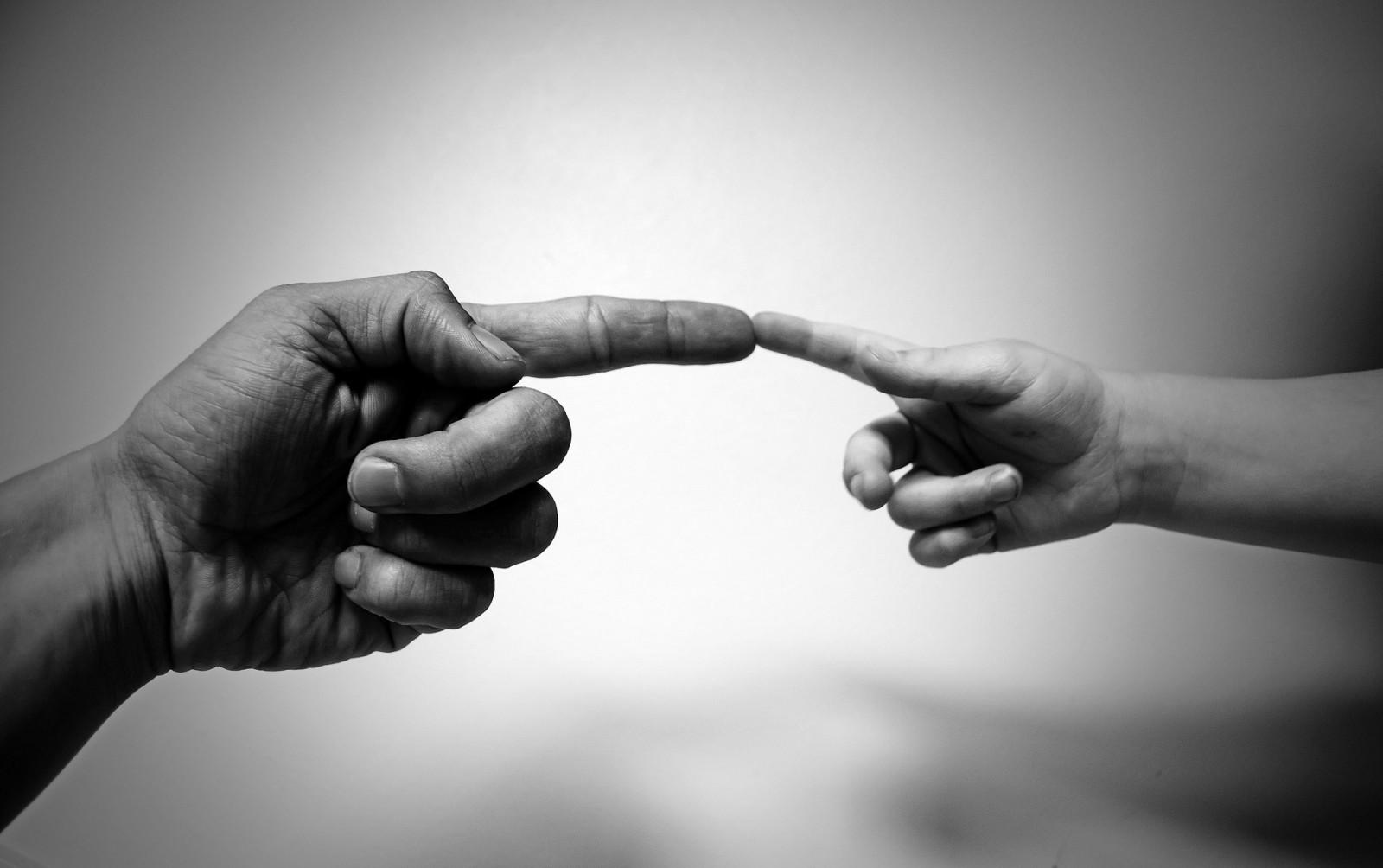 Imagen de una persona adulta con un niño juntando sus dedos índices