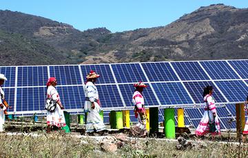 Índigenas del norte del páis caminan frente a paneles solares.