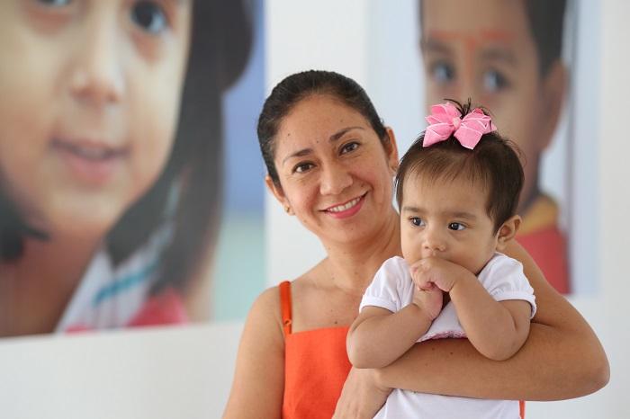 Madre sonriente sostiene a su hija de meses en los brazos. La niña con las manos en la boca, trae un moño en el pelo.