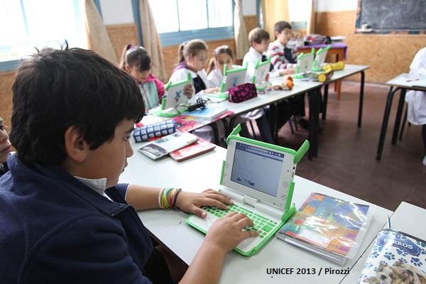 Niño y niñas usan una laptop sencilla para hacer sus primeras navegaciones en Internet, en clase escolar.