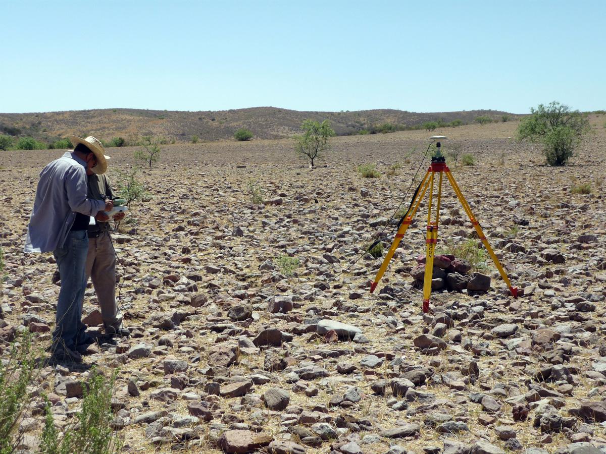 Expertos ingenieros hacen mediciones sobre una superficie en el campo.