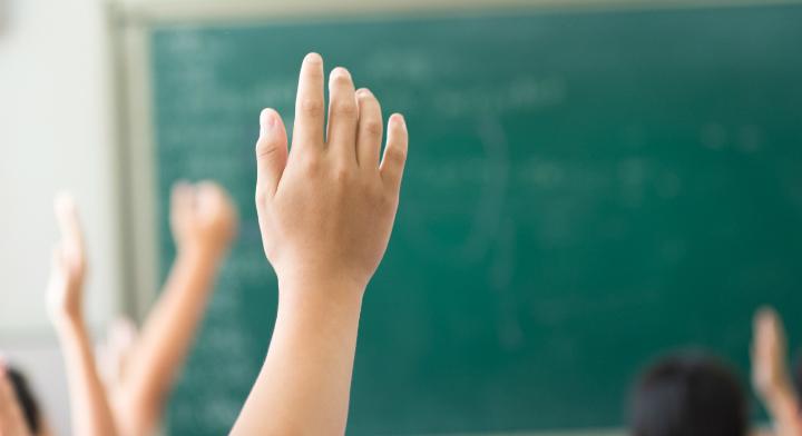 Estudiante levantando la mano, con pizarron al fondo.