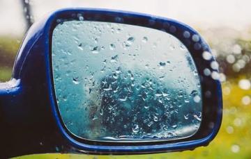 Imagen de un espejo retrovisor de un auto con gotas de lluvia