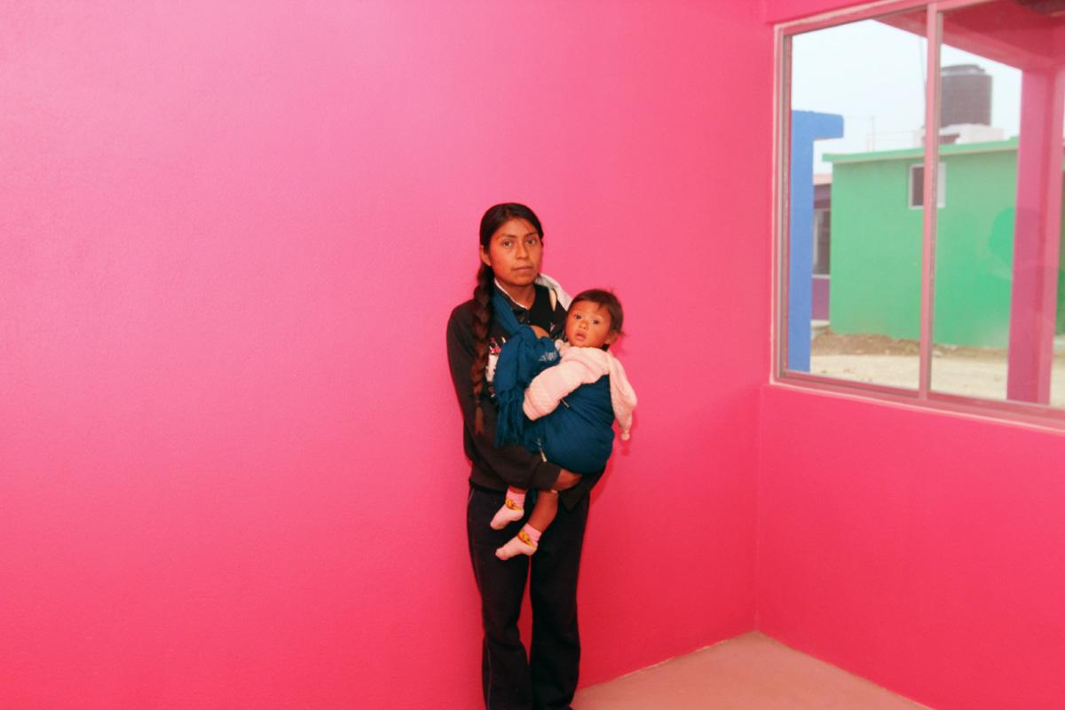 Mujer cargando a su hija en una casa rosa.