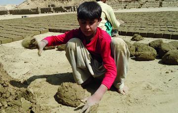 Niño trabajando en fabrica de ladrillos.
