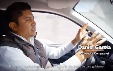 Hombre manejando en su auto y platicando su historia de éxito